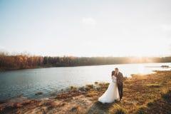 Eleganta härliga brölloppar som poserar nära en sjö på solnedgången Fotografering för Bildbyråer
