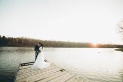 Eleganta härliga brölloppar som poserar nära en sjö på solnedgången Royaltyfri Bild