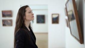 Eleganta härliga kvinnablickar för närbild på bilderna i museet av modern konst Hållande ögonen på foto för ung flicka i lager videofilmer
