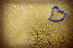 Eleganta hjärta-formade smycken i guld-färgad bakgrund. Arkivbild