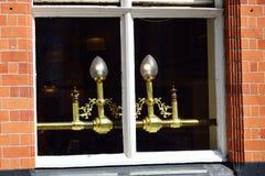 Eleganta mässingslampor i fönster royaltyfria foton