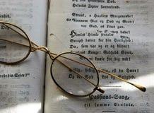 Eleganta och antika exponeringsglas på en bok Arkivbild
