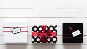 Eleganta och beautifully slågna in gåvor för för svart, röda och vita jul Arkivfoto
