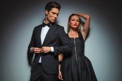 Eleganta par i svart som poserar i grå bakgrund royaltyfri bild