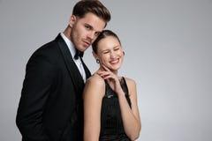 Eleganta par som poserar, medan hon skrattar royaltyfri foto