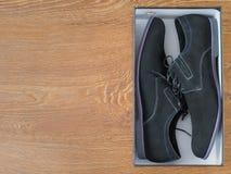 Eleganta skor för man` s i en ask på ett trägolv Arkivbilder