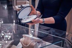 Eleganta smyckenshop'sens assistent visar den härliga pärlahalsbandet i fall att för kund arkivbild