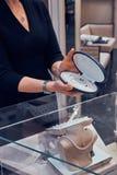 Eleganta smyckenshop'sens assistent visar den h?rliga p?rlahalsbandet i fall att f?r kund arkivfoto