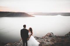 Eleganta stilfulla lyckliga brölloppar, brud, ursnygg brudgum på bakgrunden av havet och himmel Royaltyfri Fotografi
