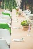 Eleganta tjänade som restaurangtabeller på träterrass Arkivfoto