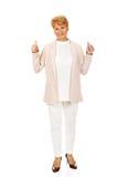 Elegante ältere Frau des Lächelns, die sich Daumen zeigt Stockbild