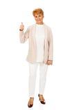 Elegante ältere Frau des Lächelns, die sich Daumen zeigt Stockbilder