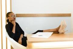 Elegante afrikanische oder schwarze amerikanische Geschäftsfrau, die tragenden Gläser, sitzend mit den Beinen in den beige Stilet lizenzfreies stockfoto
