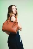 Elegante Ausstattung Stilvolle Frau mit brauner Tasche Stockbild