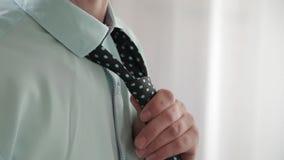 Elegante bedrijfsmens in wit overhemd die zijn band verbeteren en zijn kostuumjasje dichtknopen Sluit omhoog stock footage