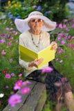 Elegante bejaarde damelezing in de tuin stock foto's