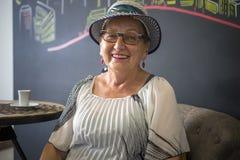 Elegante bejaardezitting in de koffieplaats royalty-vrije stock foto's