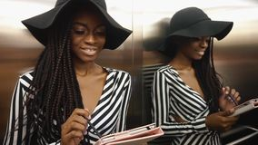 Elegante betoverende Afrikaanse Amerikaanse vrouw in een gestreepte cocktailkleding die haar tabletcomputer met behulp van stock videobeelden
