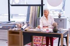 Elegante blauw-gespoelde buitensporige CEO die met documenten in haar bureau werken stock afbeeldingen