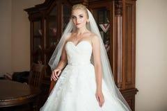 Elegante blonde Braut in der weißen Hochzeitskleideraufstellung Lizenzfreies Stockbild
