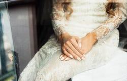 Elegante blonde Braut, die auf die Ohrringnahaufnahme, bereitend für sich setzt vor Lizenzfreie Stockbilder