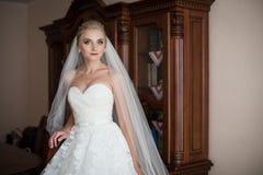 Elegante blonde Braut im weißen Hochzeitskleid Stockbild