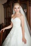 Elegante blonde Braut im weißen Hochzeitskleid Stockfotos