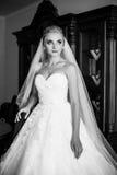 Elegante blonde Braut im weißen Hochzeitskleid, das im Hotelzimmer aufwirft Stockfoto