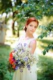 Elegante blonde Braut mit dem langen Haar und ein Blumenstrauß von Sonnenblumen Lizenzfreie Stockbilder