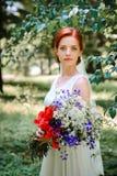 Elegante blonde Braut mit dem langen Haar und ein Blumenstrauß von Sonnenblumen Lizenzfreie Stockfotografie