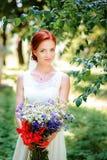 Elegante blonde Braut mit dem langen Haar und ein Blumenstrauß von Sonnenblumen Stockbild