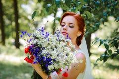 Elegante blonde Braut mit dem langen Haar und ein Blumenstrauß von Sonnenblumen Stockfoto