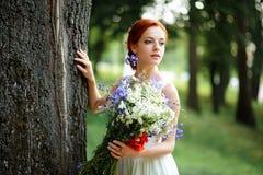 Elegante blonde Braut mit dem langen Haar und ein Blumenstrauß von Sonnenblumen Stockbilder