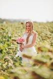 Elegante blonde Braut mit dem langen Haar und ein Blumenstrauß von Sonnenblumen auf dem Gebiet Lizenzfreie Stockfotografie