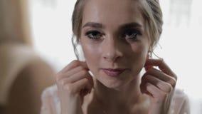 Elegante blonde Braut schöne Ohrringe tragen Frau an Heiratsmorgen stock footage