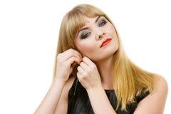 Elegante blonde Dame der Frau, die auf Ohrringe sich setzt Lizenzfreie Stockfotos