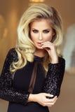 Elegante blonde Dame, die Kamera betrachtet Stockfoto