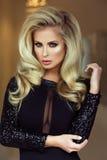 Elegante blonde Dame, die Kamera betrachtet Lizenzfreies Stockfoto