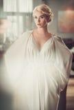 Elegante blonde Dame im beige Abendkleid im Restaurant Stockbilder