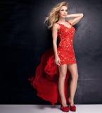 Elegante blonde Dame im roten Kleid Stockfoto
