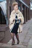 Elegante blonde Frau im Retrostil auf der Straße Stockfotografie
