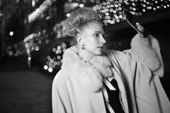 Elegante blonde Frau im Retrostil auf einem Fall, der draußen glättet Stockfoto