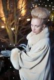 Elegante blonde Frau im Retrostil auf einem Fall, der draußen glättet Stockbild