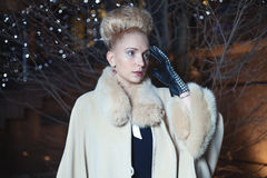 Elegante blonde Frau im Retrostil auf einem Fall, der draußen glättet Stockfotografie