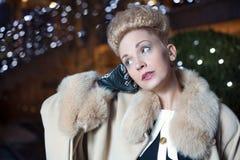 Elegante blonde Frau im Retrostil auf einem Fall, der draußen glättet Stockbilder