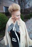 Elegante blonde Frau im Retrostil in der Herbststraße Stockfotografie