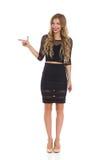 Elegante blonde Frau im schwarzem Kleiderzeigen Lizenzfreie Stockfotos