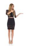 Elegante blonde Frau im schwarzen darstellenden und zeigenden Kleid Lizenzfreie Stockbilder