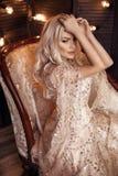 Elegante blonde vrouw in het beige kleding stellen op luxebank in koninklijk binnenland Manier mooie sensuele bruid met krullende royalty-vrije stock fotografie