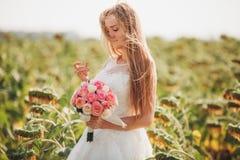 Elegante blondebruid met lang haar en een boeket van zonnebloemen op het gebied stock afbeelding
